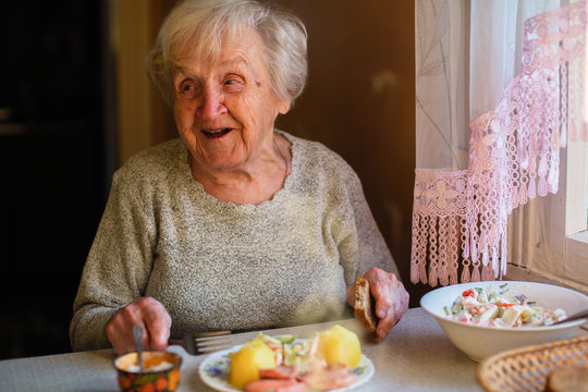 Elderly woman eat sitting at dinner table at home.