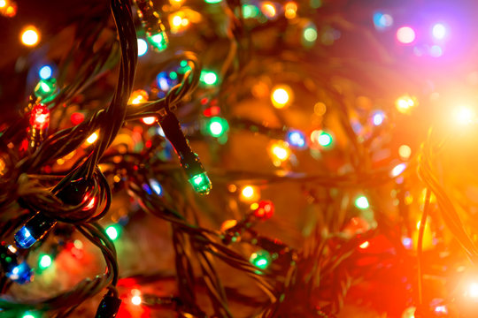Christmas blurred background. Color lights of an electric garland.