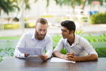 Two focused business men meeting and working in outdoor cafe. Multiethnic businesspeople sitting at table and discussing diagrams with blurred plants in background. Teamwork concept. Front view.
