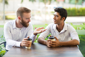 Two male friends drinking coffee and chatting in outdoor cafe. People sitting at table with blurred plants in background. Coffee break concept. Front view.