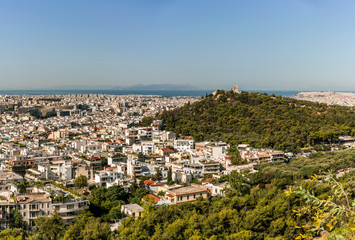 Athens city panorama with a green hill and aegean see on horizon.