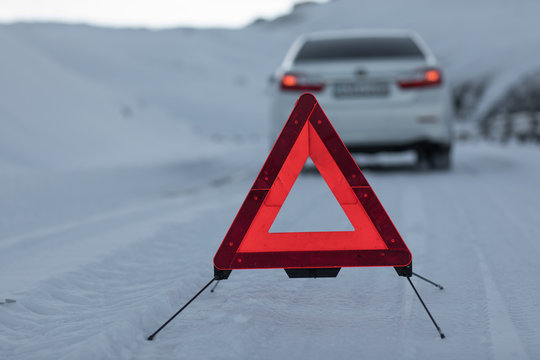 broken car and an emergency sign on a snowy road