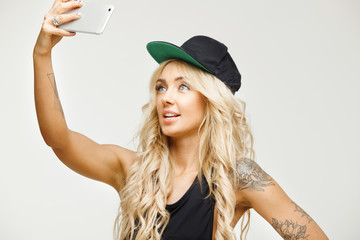 young blond woman makes selfie on front camera of smartphone over white isolated background.