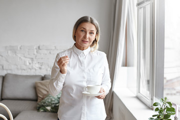 Cropped indoor shot of stylish mature businesswoman dressed in long white blouse standing in modern apartment interior at large window holding mug, enjoying morning coffee before working day