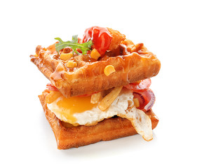Delicious waffles with fried egg on white background
