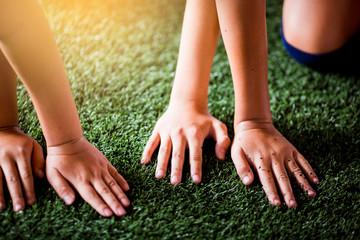 Children's hands on green artificial turf.