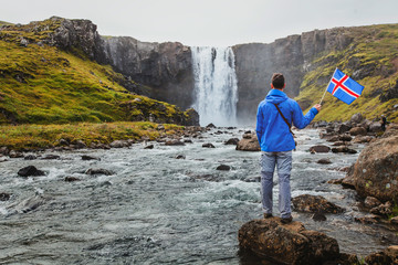 travel to Iceland, tourist holding icelandic flag near scenic waterfall