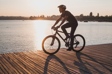 Poster Cycling silhouette of man on bicycle in sunset city near lake, sport cycling active leisure