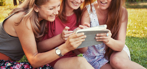 summer shopping online, people using social media, group of girls friends looking at tablet computer and smiling