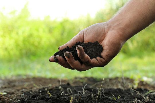 Man holding black soil outdoors