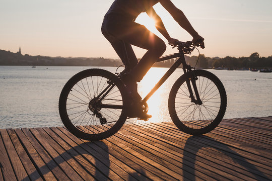 man riding bicycle at sunset, cycling in summer, silhouette of cyclist near the lake