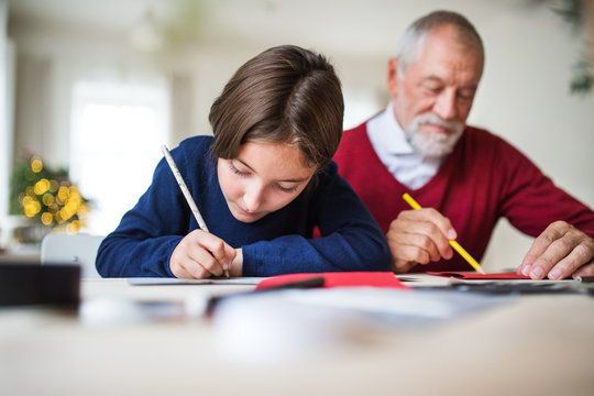 A small girl and her grandfather writing Christmas cards together.
