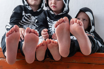 Happy children in carnival outfits, boys with a red crocodile in the studio. Black suit with the image of skeletons. Classic halloween costume. Funny family kids childhood