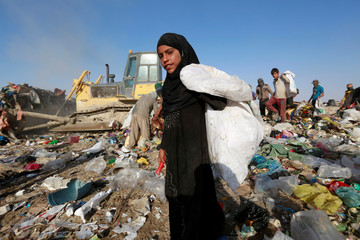 A girl carries a bag of garbage to be sorted and sold to recycling centres in Najaf