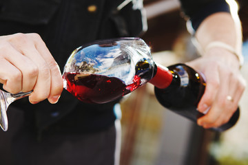 Man pouring wine into wineglass, male hand holding bottle