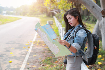 Young asian traveler searching direction on location map while traveling during holiday vacation.