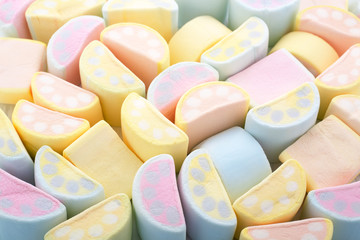 Marshmallows in crescent shape. Pastel colors trendy background or texture of colorful mini marshmallows. Top view, close-up.