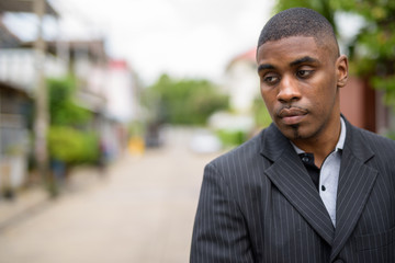 Young handsome African businessman wearing suit in the streets o