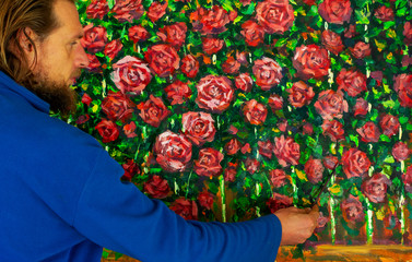 Male artist paint Red rose flowers painting in the studio. Creative process.
