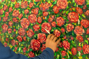 Male hand paint draw beautiful picture red roses oil painting with palette knife.