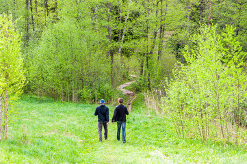 Two men walking on bent pathway into the woods