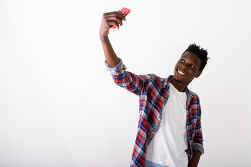 Studio shot of young happy black African man smiling while takin