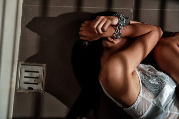 sexual assault and imprisoned woman in jail with chain waiting for help (this image for girl victim and violence concept)