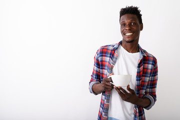 Studio shot of young happy black African man smiling while holdi