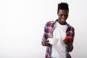 Studio shot of young happy black African man smiling and holding