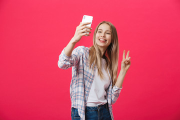 Charming young woman in white hat travel and take selfie on front camera smartphone posing isolated on shine pink background