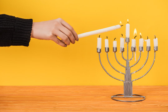 partial view of woman lighting candles on menorah isolated on yellow, hannukah holiday concept