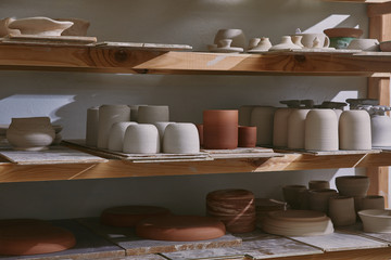 Obraz ceramic bowls and dishes on wooden shelves at pottery studio - fototapety do salonu