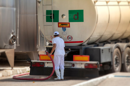 Male worker loading truck container with milk in an industrial cheese production factory