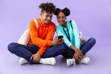 African american man and woman wearing backpacks using smartphone and earphones while sitting on floor with legs crossed, isolated over violet background