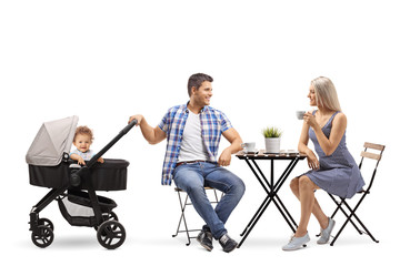 Young family of a mother, father and a baby in a stroller sitting in a cafe
