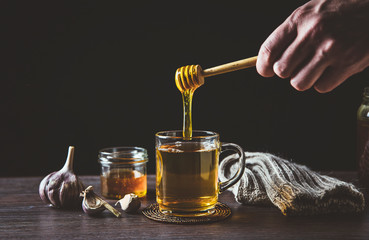 Man hand holding wooden honey dipper, honey spoon on top of glass of tea/ medicine and dripping honey in hot tea. Knitted socks, small jar of honey, garlic on wooden table against black background.