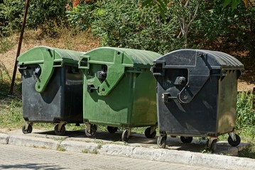 three large dumpsters on the street by the road