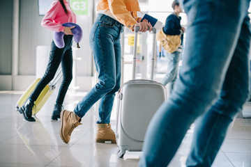 low section of young people with suitcases in airport terminal