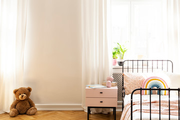 Teddy bear on a floor in a teenage room interior with an empty wall. Place your graphic. Real photo