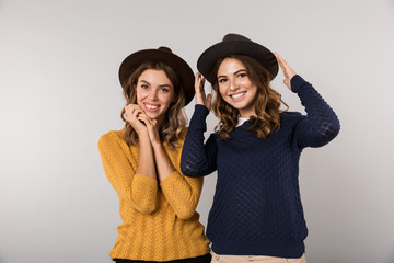 Image of two cheerful women wearing hats smiling at camera, isolated over gray background