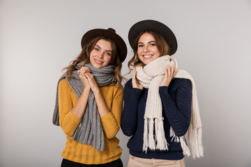 Image of two cheerful women wearing hats and scarfs smiling at camera, isolated over gray background