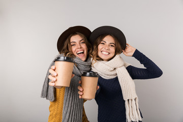Image of two happy women wearing hats and scarfs holding takeaway coffee in paper cups, isolated over gray background
