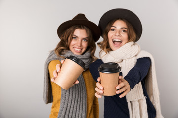 Image of two joyous women wearing hats and scarfs holding takeaway coffee in paper cups, isolated over gray background