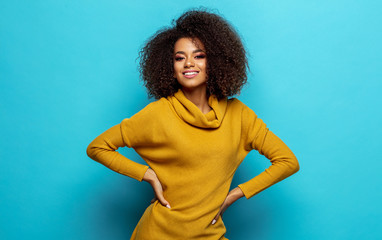 Wall Mural - Smiling black woman wear cardigan isolated on blue background