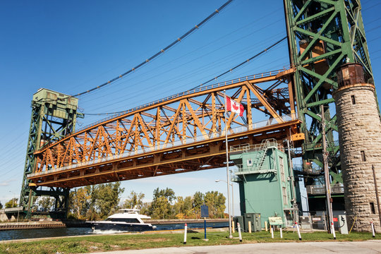 The Burlington Canal Lift Bridge in Hamilton, Ontario, Canada. A vertical-lift bridge over the canal connecting Burlington Bay with Hamilton Harbour on Lake Ontario. In use, with a private vessel.