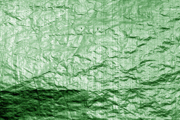 Crumpled transparent plastic  surface in green color.