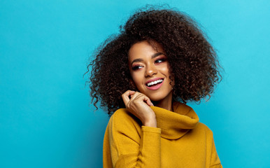 Wall Mural - Beautiful smiling african american woman with an afro hairstyle looking on empty space isolated on blue background