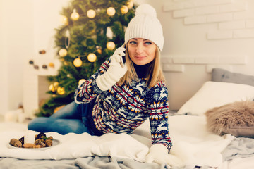 Woman relaxing in a bed and using mobile phone at christmas