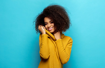 Wall Mural - Smiling black woman wear yellow cardigan isolated on blue background