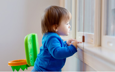 Little toddler boy looking out the window